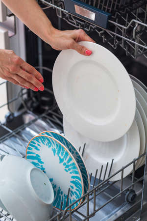 household chore: Womans hand putting a white plate into the dishwasher; a household chore Stock Photo