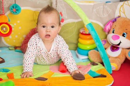 Eight months old baby girl playing with colorful toys on a floor mat  Stock Photo