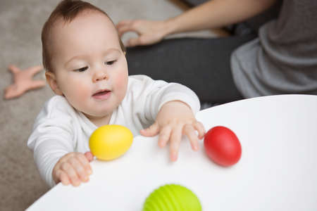 Nine months old baby girl trying to grab colorful toy eggs on the white table; mother sitting by her side Stock Photo