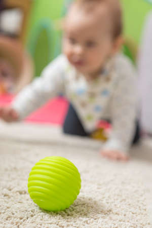 Nine months old baby girl crawling on the floor towards the green toy ball; shallow depth of field, focus on the ball