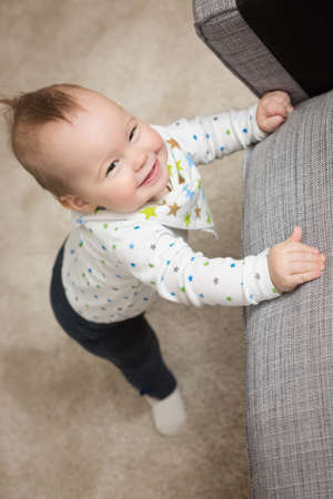 learnt: Nine months old baby girl standing on her feet in an effort to climb up the sofa; baby just learnt how to stand on her feet Stock Photo