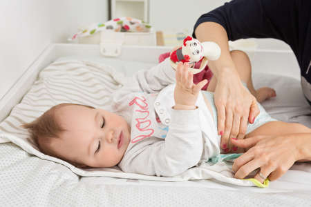 Mother changing diapers of a nine months old baby girl daughter; child laying on the desk in the nursery, mothers hands visible