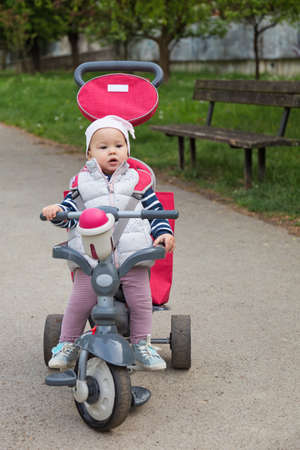 One year old baby girl sitting in a red and grey tricycle in the park by the wooden bench