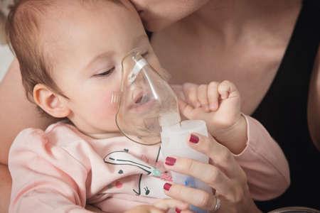 흡입기, 팔에 그녀를 들고 그녀의 머리에 그녀의 키스 아픈 아기를 위로하는 그녀의 어머니에서 흡입 한 살짜리 아기 소녀 스톡 콘텐츠