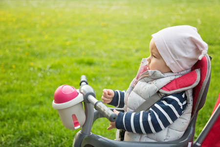 One year old baby girl sitting in a red and grey tricycle in the park, against the sunlit grass