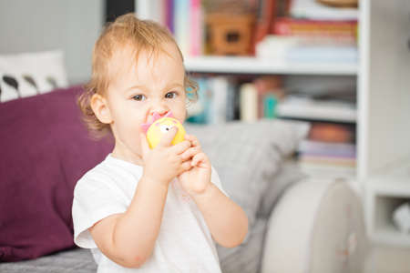 One and a half year old toddler baby girl sucking her toys in the living room Stock Photo