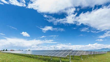 Paneles de la planta de energía solar bajo el cielo azul con nubes blancas - concepto de energía limpia Foto de archivo