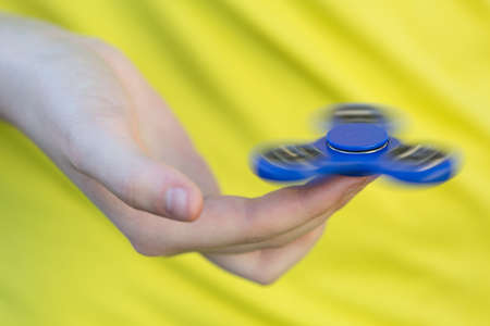 Girls hand holding a spinning fidget spinner in her hand, spinning them on her index finger
