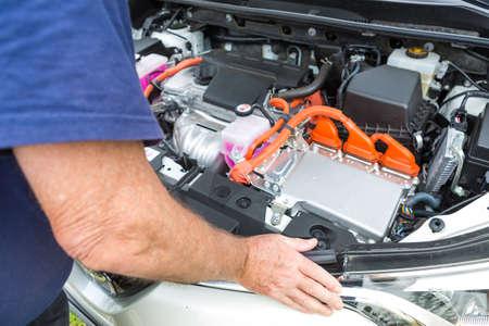 ハイブリッド車の内部に傾いている年配の男性は両方のバッテリとガスの電気エンジンによって供給 写真素材