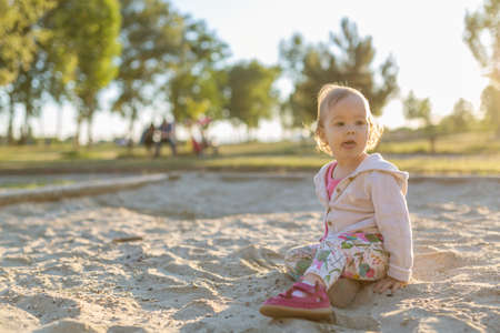 fifteen: Fifteen months old baby girl playing in the sandbox in the sunset