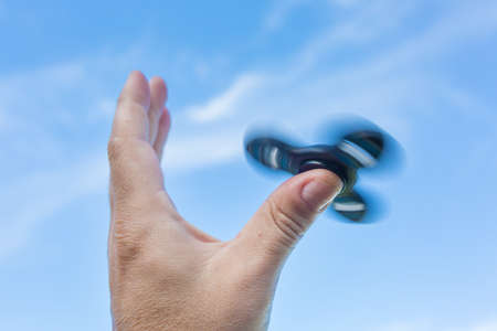 Mans hand holding a spinning fidget spinner in his hand, spinning them on his thumb, against the blue sky Stock Photo