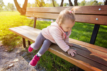 Eighteen months old toddler girl climbing on the wooden bench in the park on a sunny autumn day