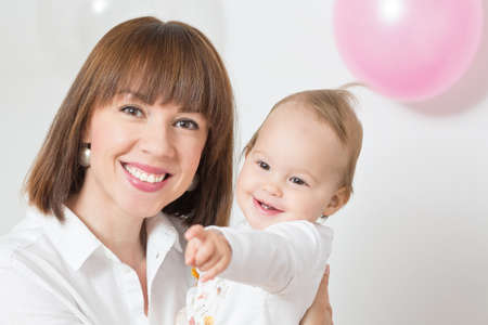 Mother holding an one year old baby daughter and smiling, baby girl pointing her finger Reklamní fotografie