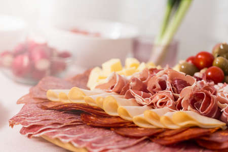 Tray with bacon, cheese cubes, salami, ham; with spring onions in the background Archivio Fotografico