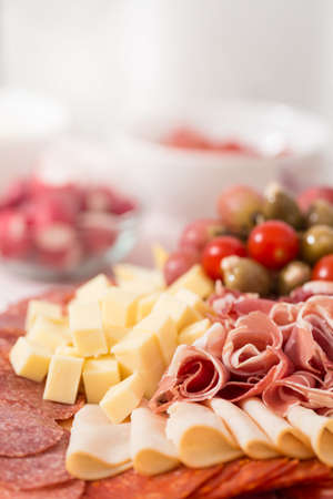 Tray with bacon, cheese cubes, salami, ham; decorated with grapes