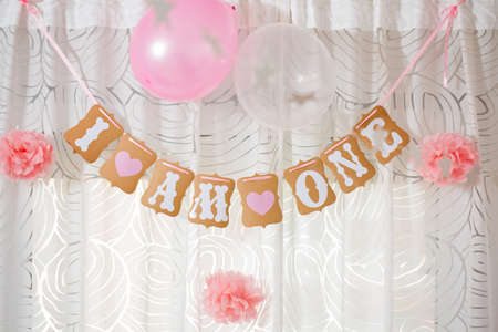 Baby birthday decoration hanging from the ceiling, with letters forming words I am (loved) one; in celebration of babys first birthday
