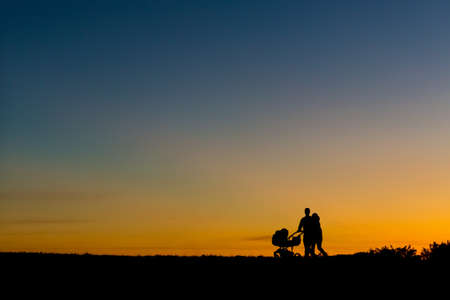 Sillhouette of a young couple walking during sunset with a baby in the stroller