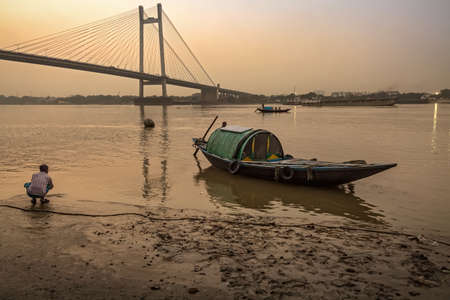 hooghly: KOLKATA, INDIA - NOVEMBER 11, 2016: A wooden country boat used for pleasure boat rides lined up at Princep Ghat on river Hooghly at dusk. The Hooghly river bridge at the backdrop.