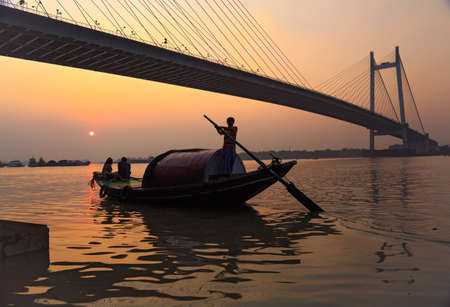 Wooden boat on river Hooghly at sunset with Vidyasagar bridge at the backdrop (silhouette),