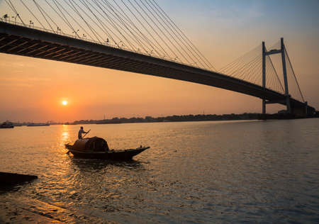 hooghly: Wooden country boat on river Hooghly at sunset with Vidyasagar bridge at the backdrop (silhouette)Kolkata, India.
