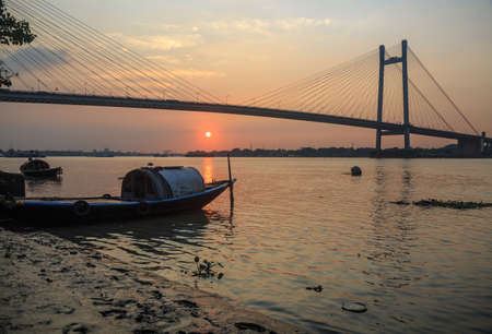 hooghly: Wooden boat on river Hooghly at sunset with the Vidyasagar bridge at the backdrop. This is known to be the longest cable stayed bridge in India. (silhouette view)