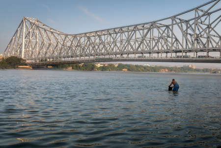 hooghly: Historic Howrah bridge on the river Hooghly (Ganges). An unidentified man take a holy dip in the water of the ganges.