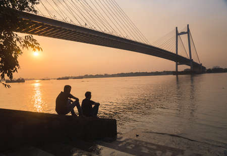 hooghly: Two friends enjoy the sunset view on river Hooghly with Vidyasagar setu (bridge) at the backdrop at Princep Ghat, Kolkata, India. Photograph taken at Princep Ghat on November 14, 2016.