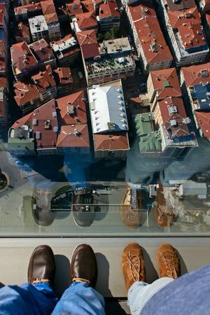 vertigo: A pair of feet on the edge of a tall building ledge looking down into a city of highrise.
