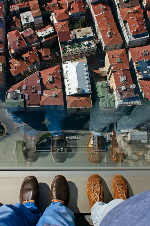 A pair of feet on the edge of a tall building ledge looking down into a city of highrise.