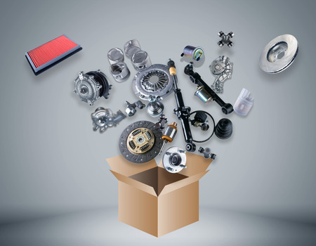 spare car: Many spare parts flying out of the box on grey background