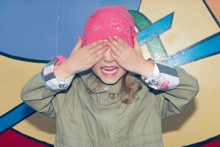 hide and seek: Little girl is playing hide and seek hiding face