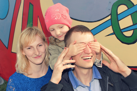 hide and seek: Father, mother and daughter making a joke or playing hide and seek