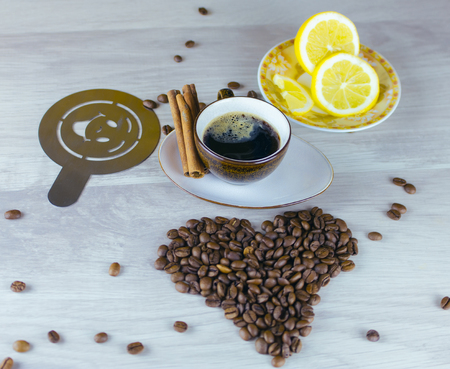 close up view: Coffee beans and coffee cup on table with lemon