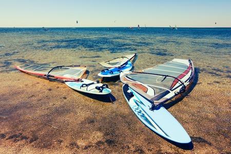 windsurf: tabla de windsurf multicolor que miente en las orillas de la r�a. El mejor lugar para aprender windsurf. tablas de windsurf con velas. windsurf entrenamiento de verano. Mar, Deporte y windsurf.