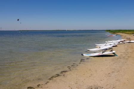 windsurf: tabla de windsurf multicolor que miente en las orillas de la ría. El mejor lugar para aprender windsurf. tablas de windsurf con velas. windsurf entrenamiento de verano. Mar, Deporte y windsurf.