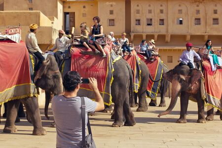 3rd ancient: Jaipur, India, november 10, 2011: Indian elephant riders ride with tourists to Amber Fort. Man with mobile phone taking pictures of tourists on elephants.
