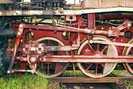 peron: Old, vintage locomotive which stands on the rails. Rusty and dirty train wheels close up. The train made in the distant past. Stock Photo
