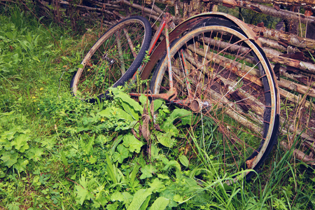 trashed: Old broken vintage rust bicycle lying in the grass Stock Photo