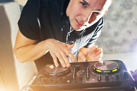 Young man DJ with headphones is working on turntable console mixer controlling