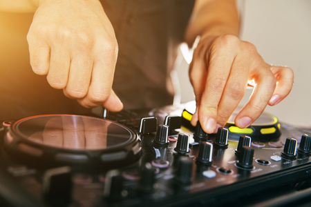 DJ turntable console mixer controlling with two hand in concert nightclub stage. Stock Photo