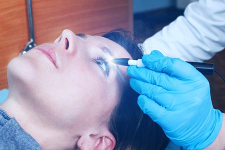 眼科の医師は、若い女の子の視力、眼球を診断する演算を行います。仮想レーザー ビジョンをチェックします。