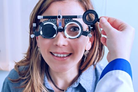 Girl woman in messbrille glasses in ophthalmology clinic. Ophthalmic glasses for diopter detection. Stock Photo