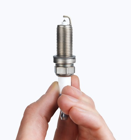 Mechanic holds a spare part spark plug in his hand. Auto part spark plug close-up on a white background. Stock Photo