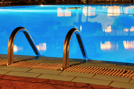 Pool at night. Blue water and handrails to enter the water.