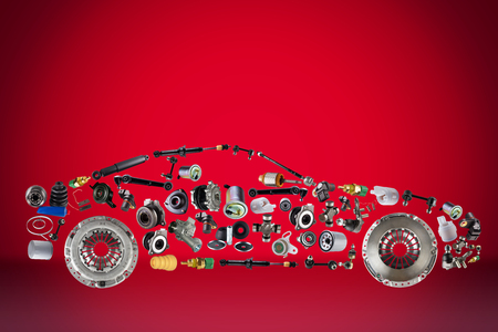 Passenger car assembled from new spare auto parts for shop aftermarket. Isolated on red background. Archivio Fotografico