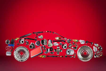 Passenger car assembled from new spare auto parts for shop aftermarket. Isolated on red background. Stock Photo