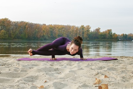 A young girl practices yoga by the river. Exercises against the background of the river, the shore and the bridge.
