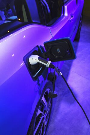 EV Car or Electric car at charging station with the power cable supply plugged. Eco-friendly alternative energy concept