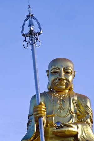 Gold Buddha Statue on blue sky background