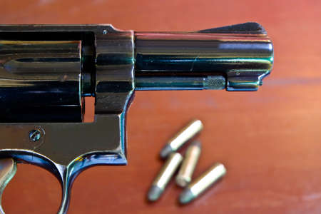 Revolvers backdrop brown wooden desk with a bullet.